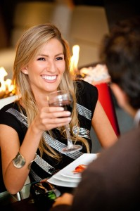 woman smiling holding a glass of wine with white teeth