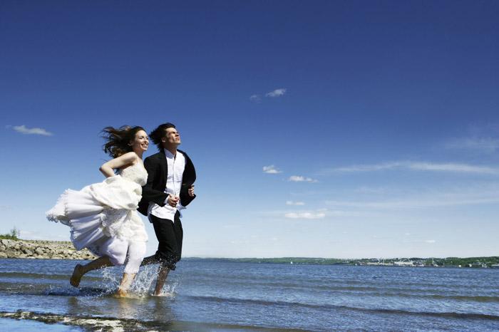 bridge and groom running on the beach